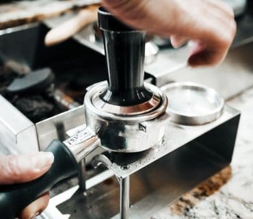barista-is-pressing-ground-coffee-in-the-cafe-shop
